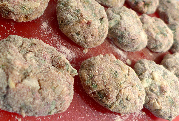 Step 3: Place all coated meatballs onto a cutting board or tray and flatten slightly into patties.